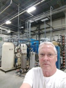 Wastewater Operator in front of tank